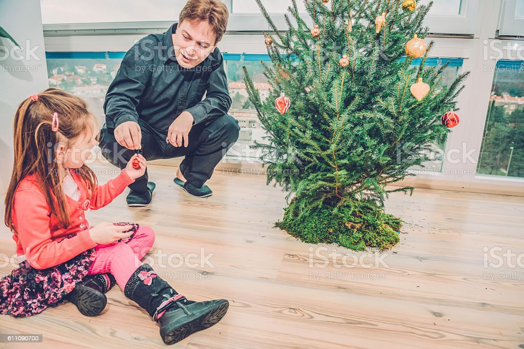 Cute Girl in Pink and Father Decorating Christmas Tree, Europe stock photo