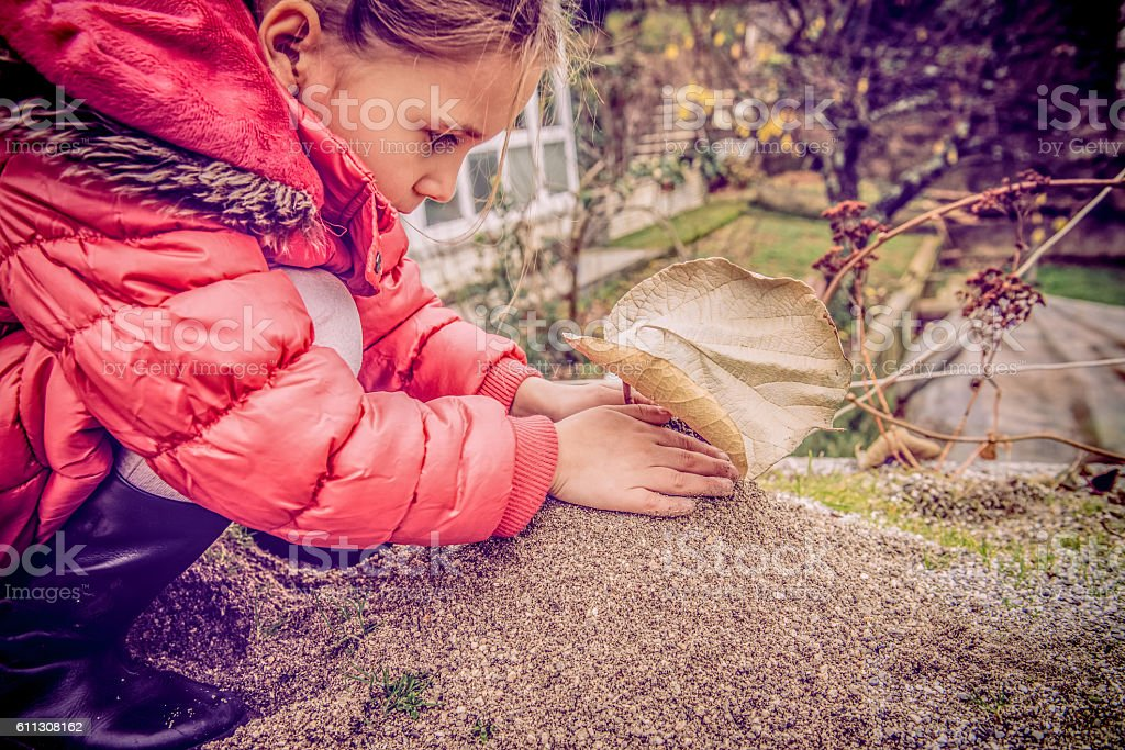 Cute Girl in Pink Coat  Playing with Sand, Winter, Europe stock photo