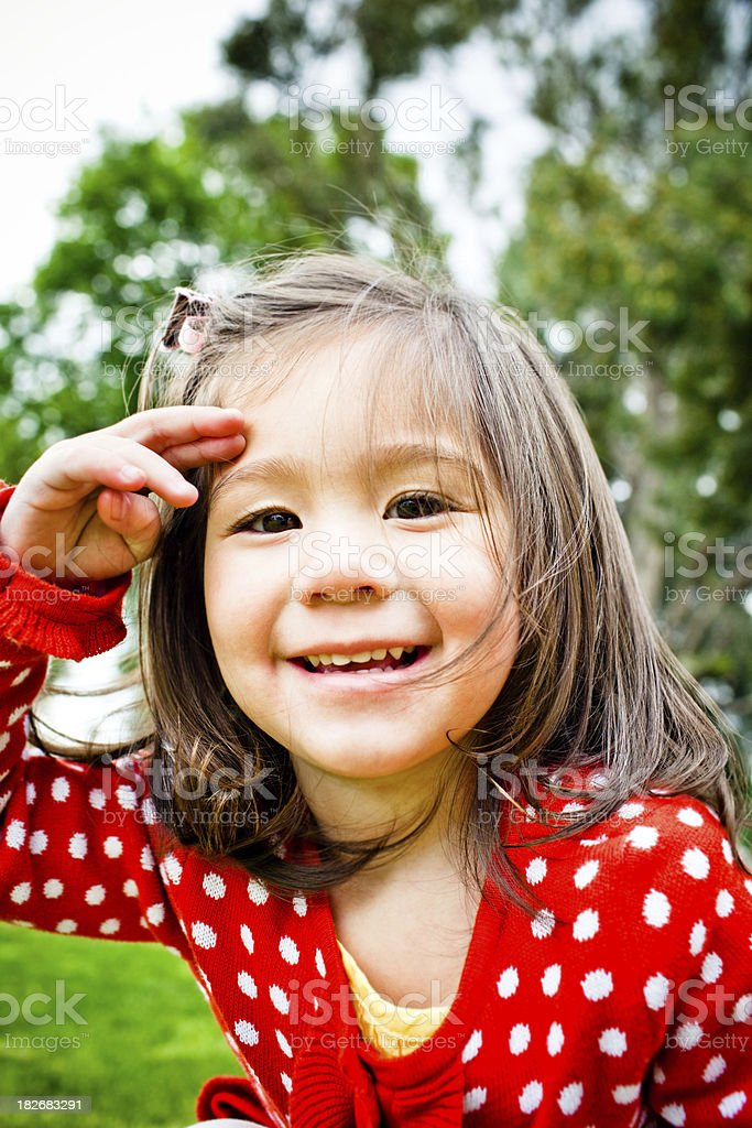 cute girl in red sweater saluting royalty-free stock photo