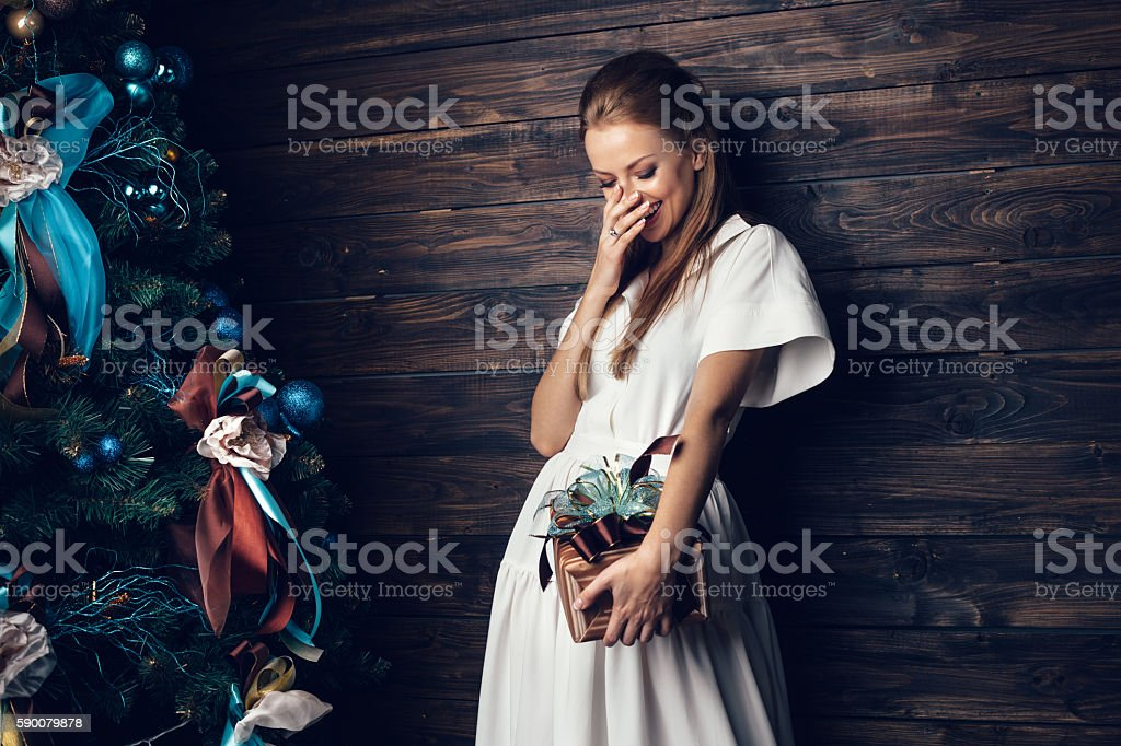 Cute girl in white dress holding gift box over wood wall background,...