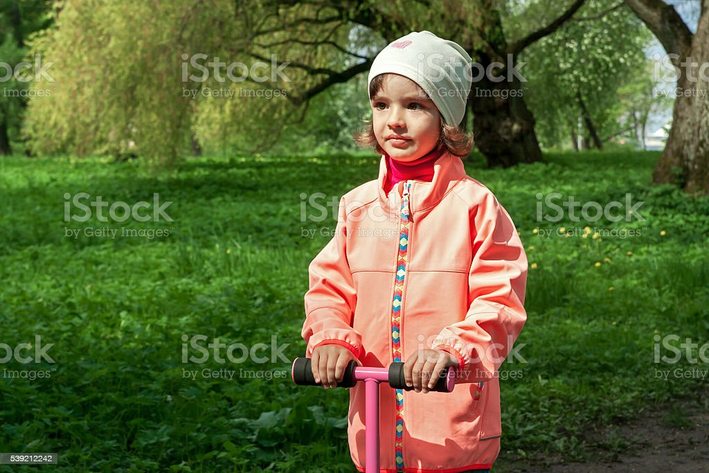 Cute girl is walking in a beautiful green park stock photo
