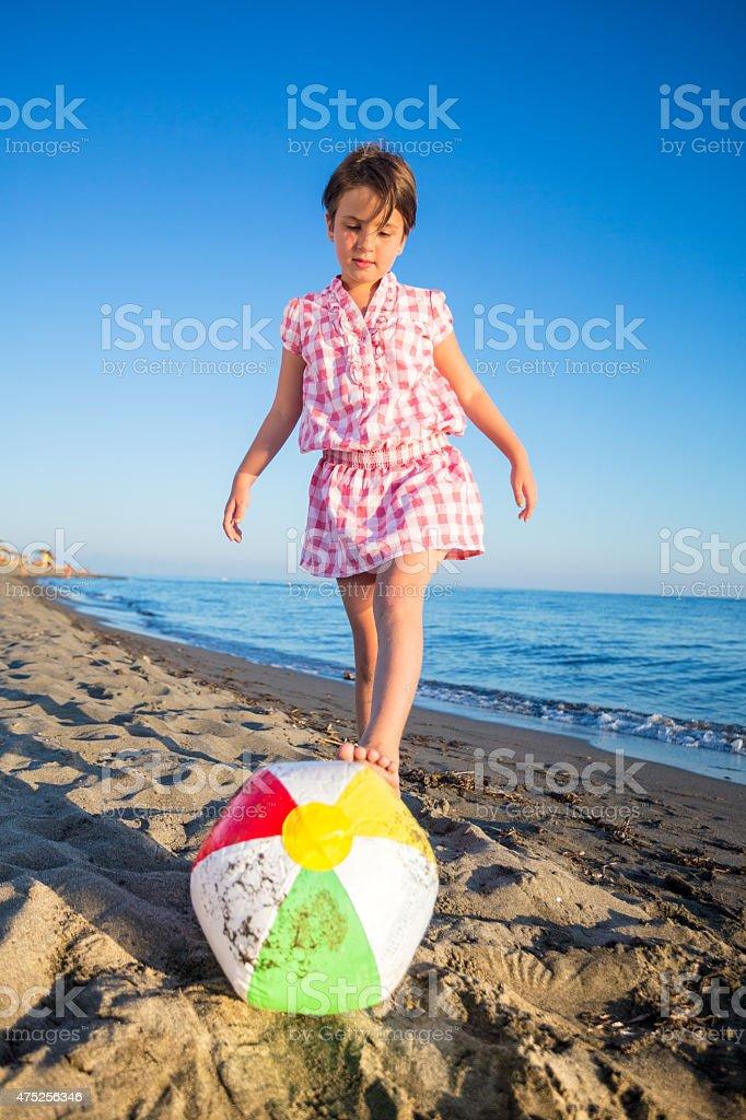 Cute girl kickinc beach ball stock photo