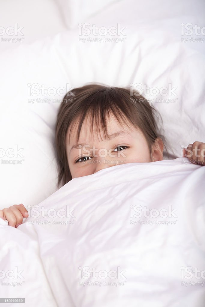 Cute girl laying under duvet stock photo