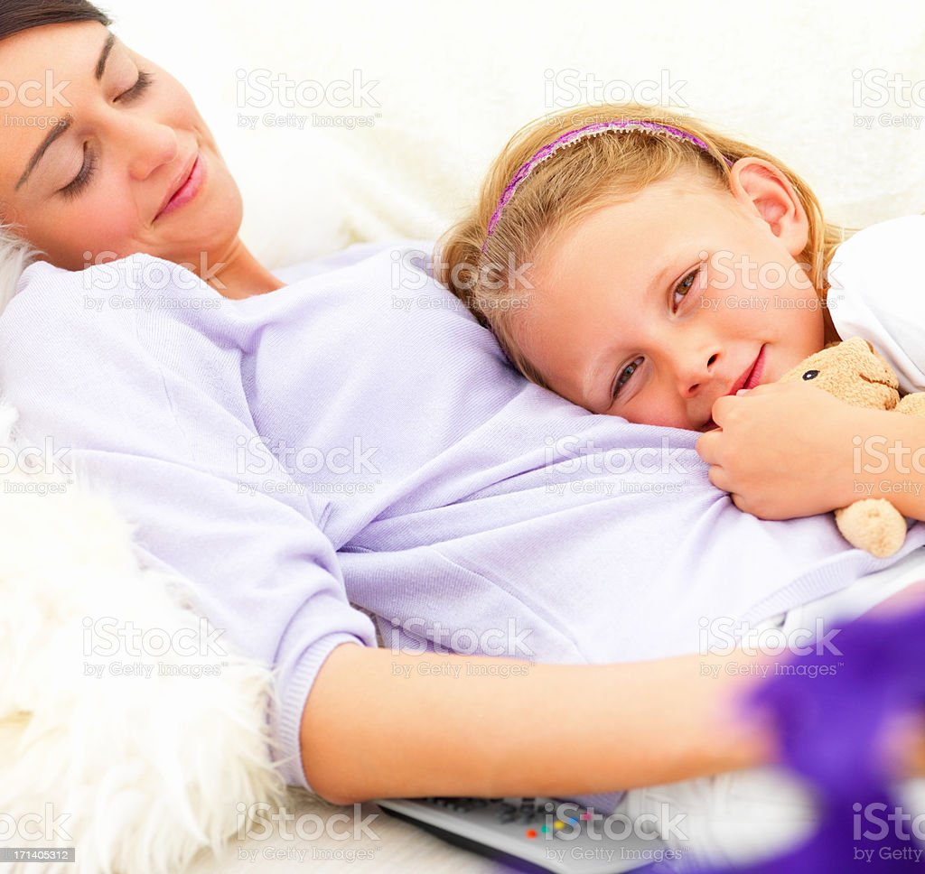 Cute girl lying on her mother at home stock photo