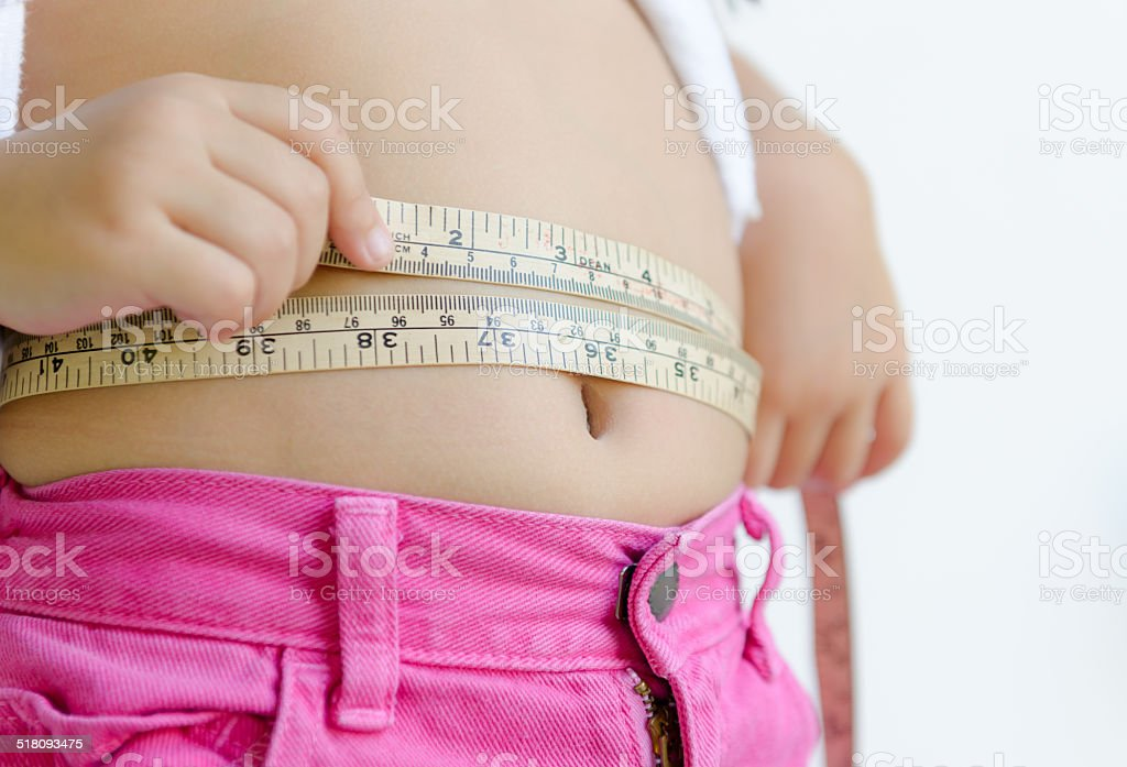 cute girl measuring her belly with measurement tape stock photo