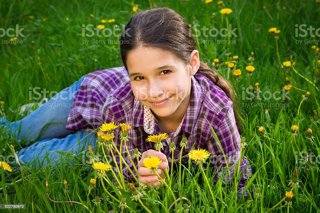 Cute girl on field with dandelions stock photo