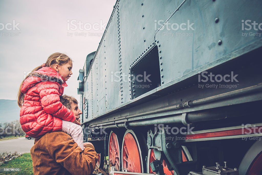 Cute Girl on Grandfather's Shoulders Observing Old Steam Locomotive,  Europe stock photo