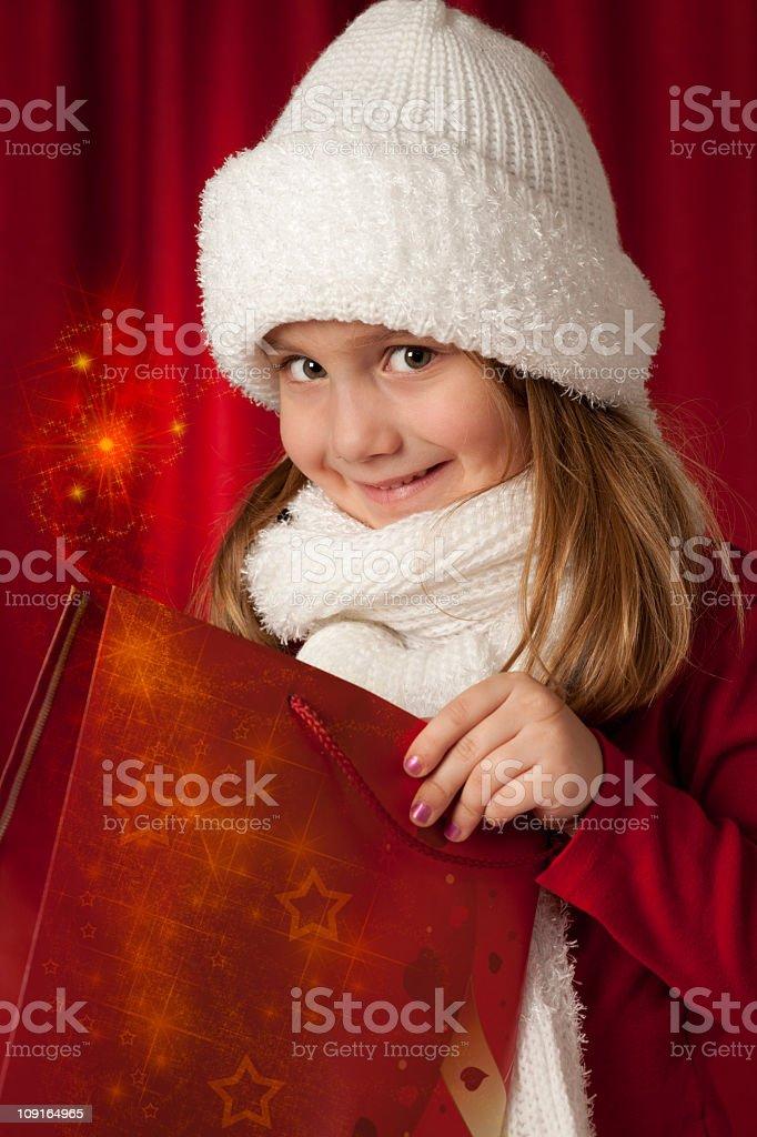 Cute girl opening her gift (Christmas magic) stock photo