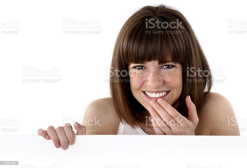 Cute girl peeking up behind white wall royalty-free stock photo