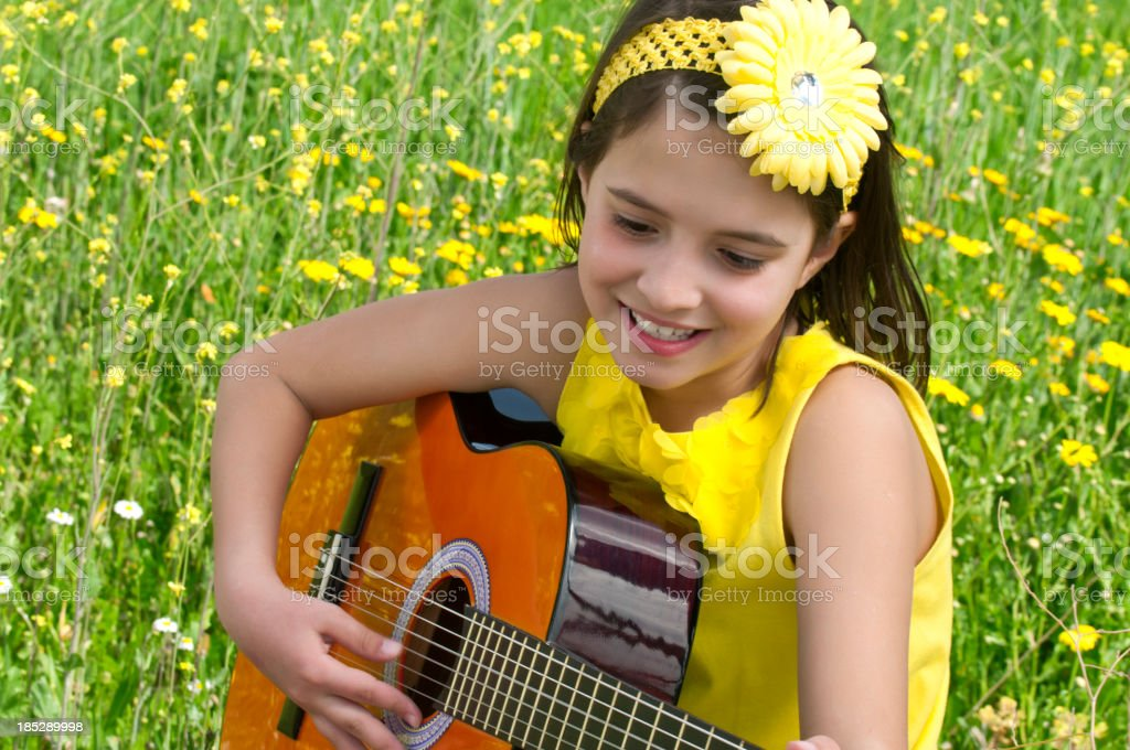 Cute girl playing guitar to daisy field stock photo