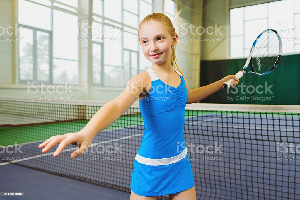 Cute girl playing tennis and posing in court indoor stock photo