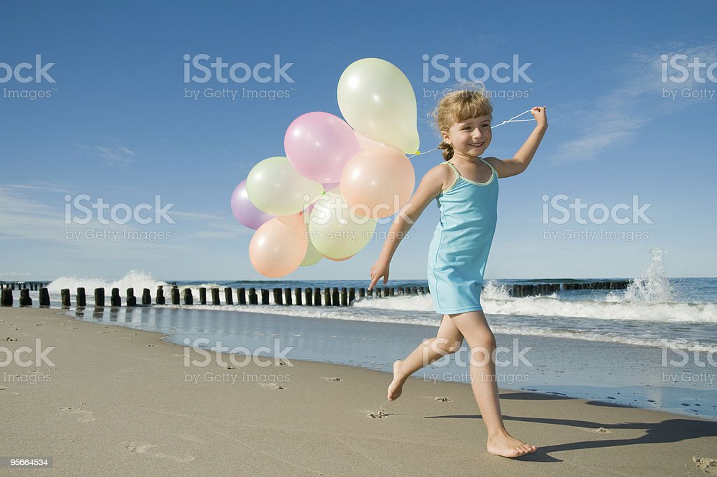 Cute girl playing with balloons at the beach royalty-free stock photo
