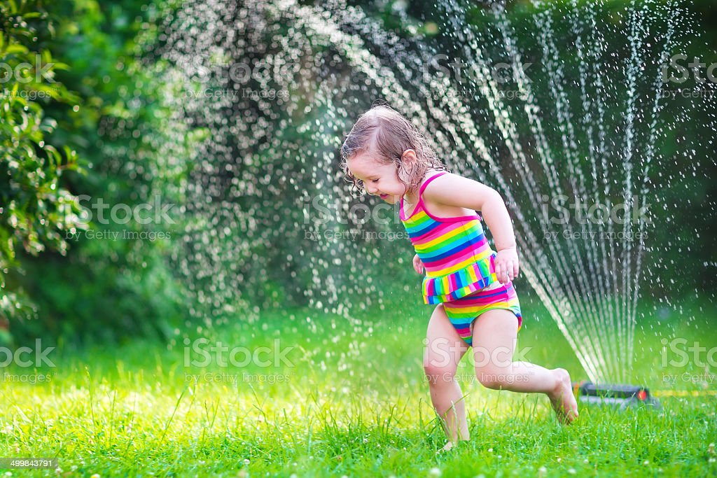 Cute girl playing with garden sprinkler stock photo