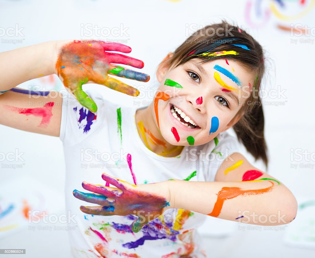 Cute girl playing with paints stock photo