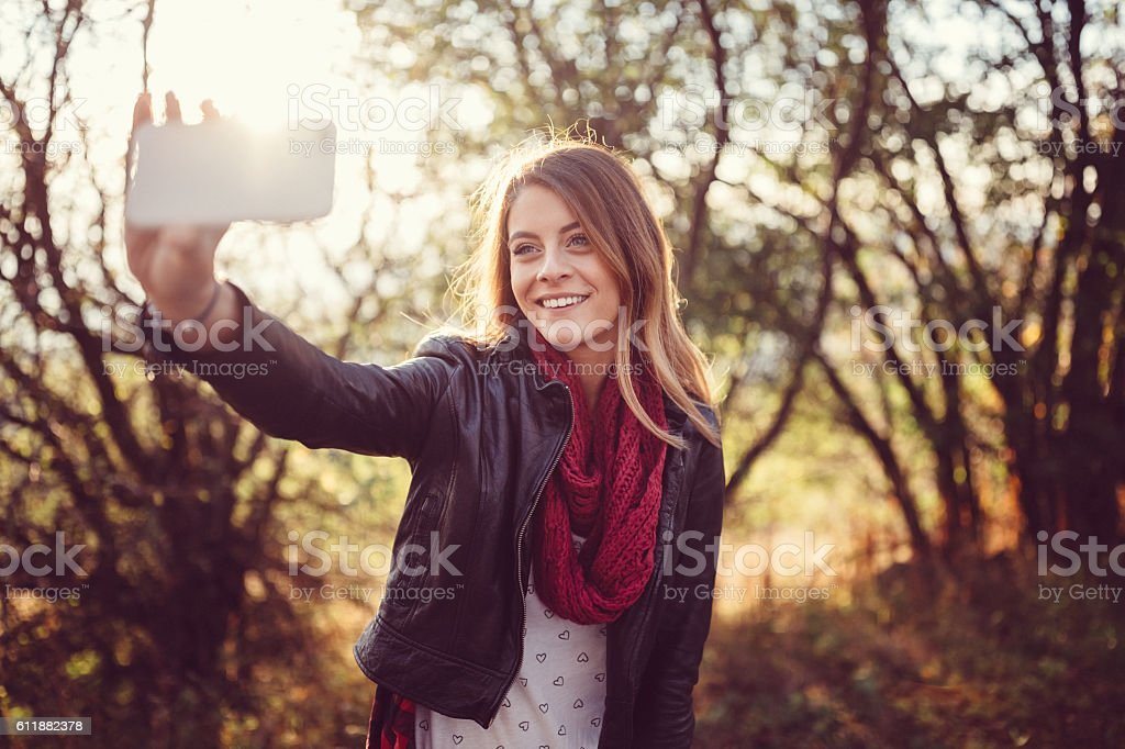 Cute girl posing for selfie among nature stock photo