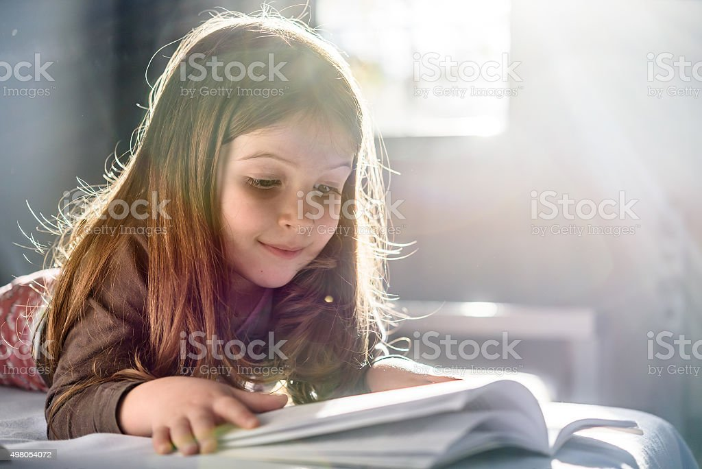 Cute Girl Reading a Book at Home stock photo
