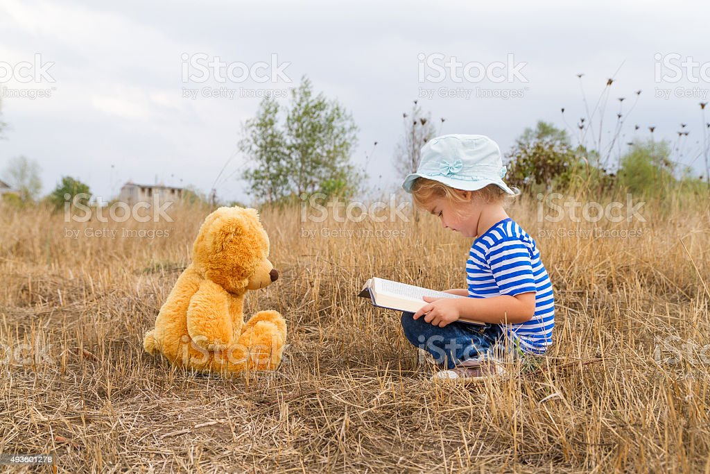 Cute girl reading book Teddy bear stock photo