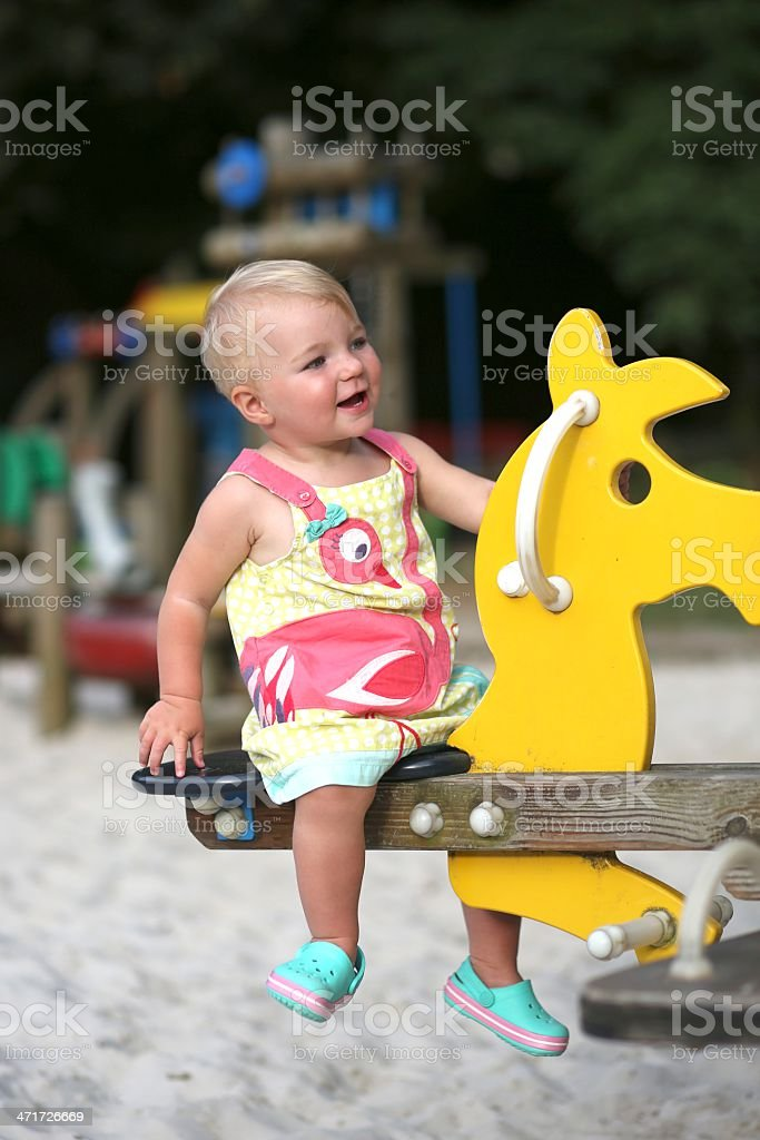 Cute girl riding a spring horse in the playground stock photo