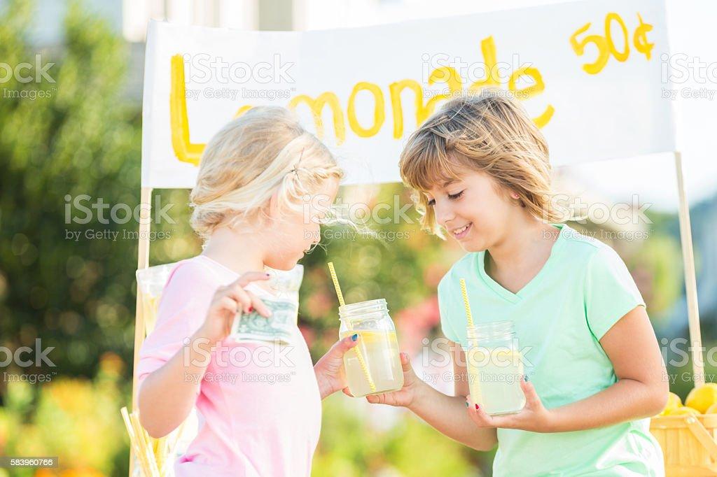 Cute girl selling glass of lemonade at her lemonade stand stock photo