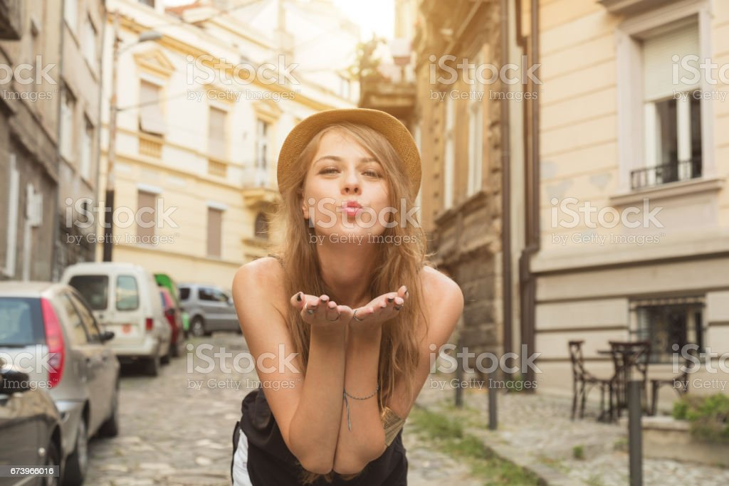 Cute girl sending air kiss outdoors. stock photo