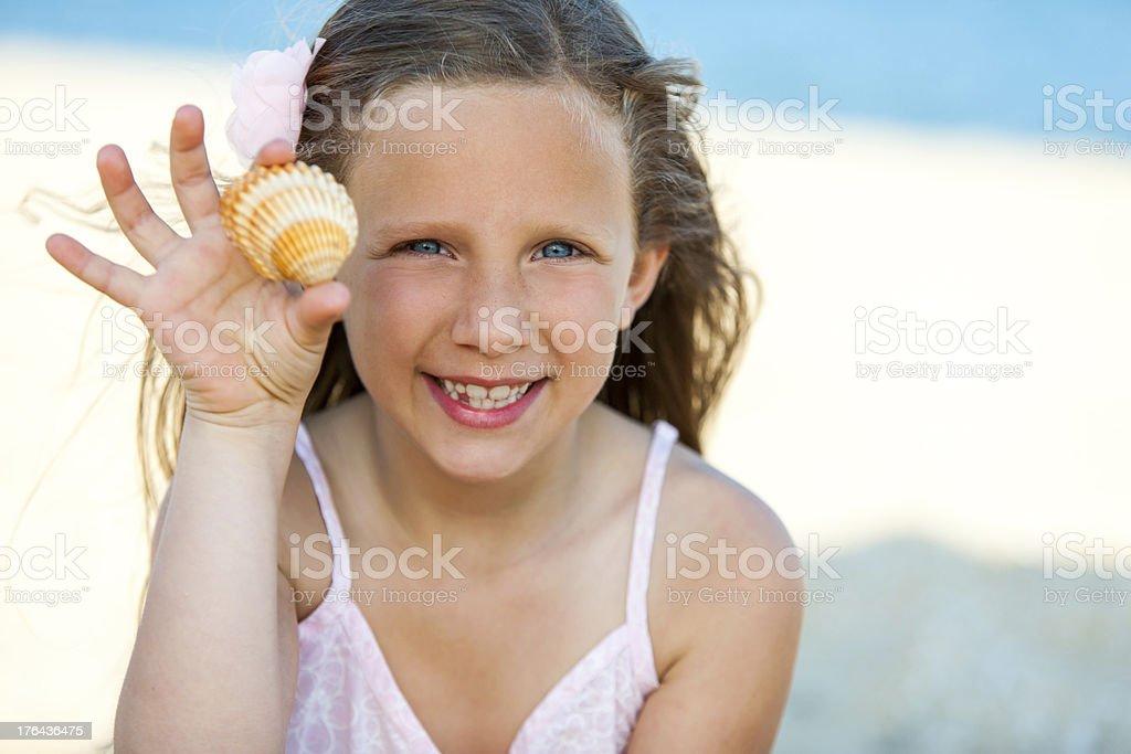 Jolie fille montrant des coquillages sur la plage. photo libre de droits