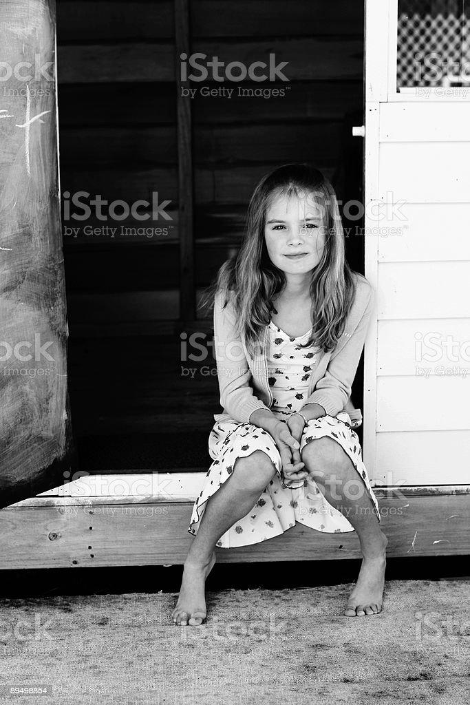 Cute girl sitting in doorway stock photo