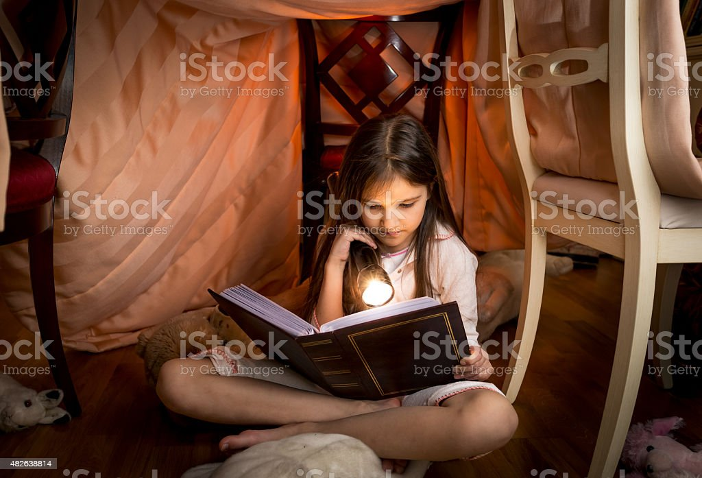 cute girl sitting under blanket and reading a book stock photo