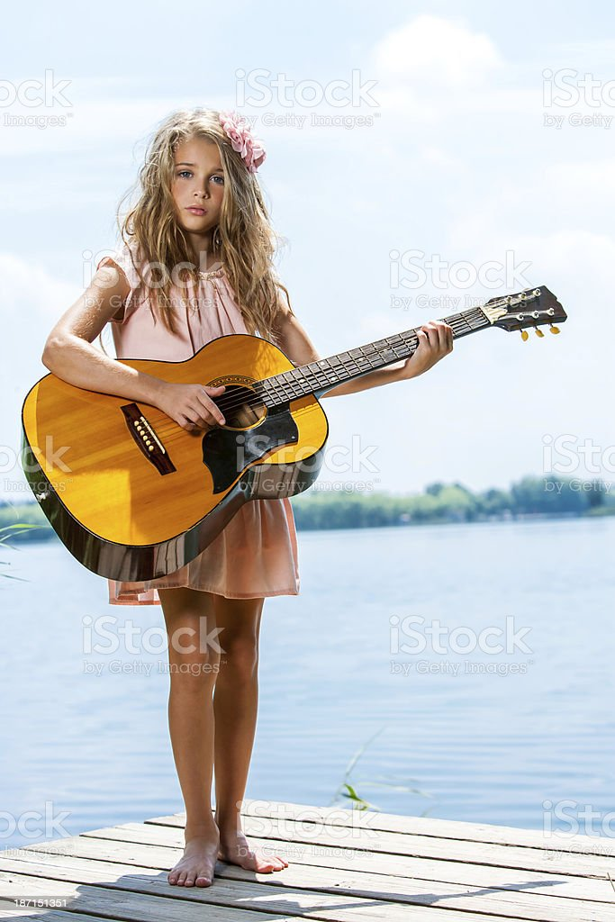 Cute girl standing with guitar at lake. royalty-free stock photo
