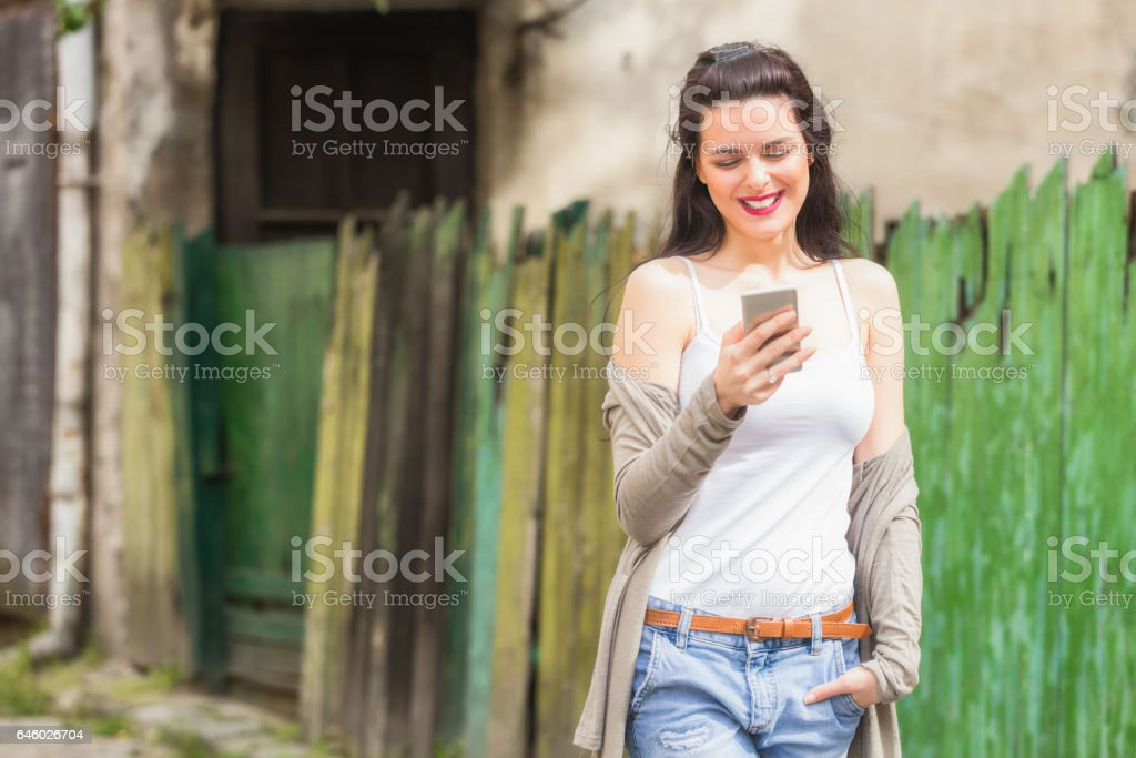 Cute girl using cellphone on the street. stock photo