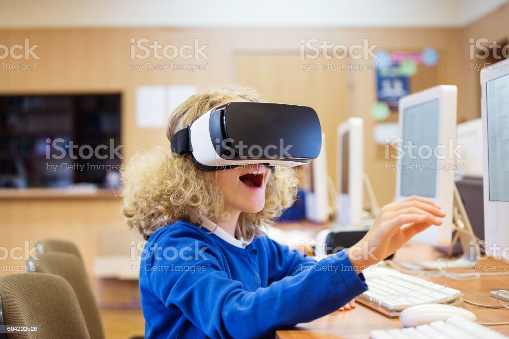 Cute girl using virtual reality goggle at school stock photo