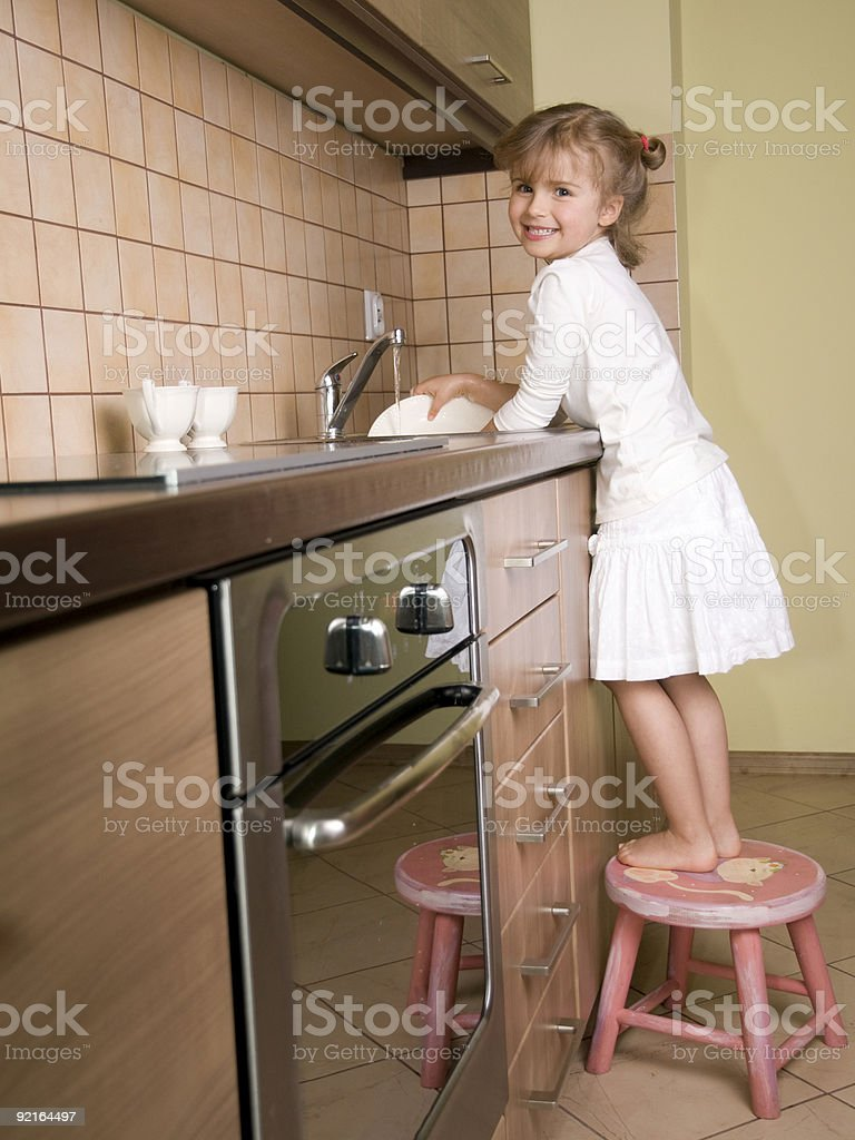 Cute girl washing the dishes royalty-free stock photo