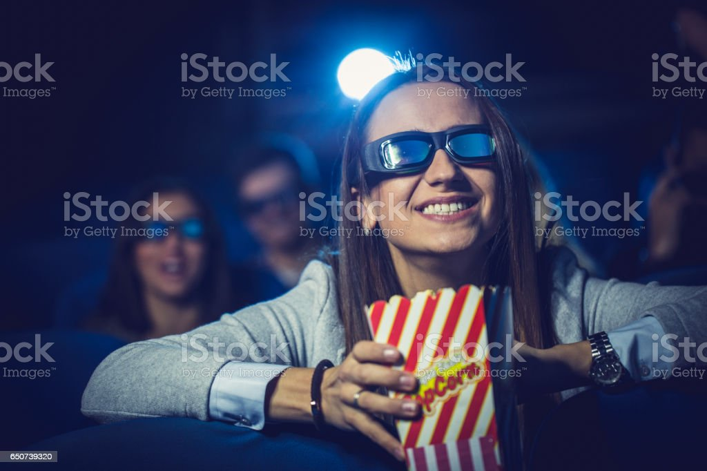 Cute girl watching a movie with friends stock photo