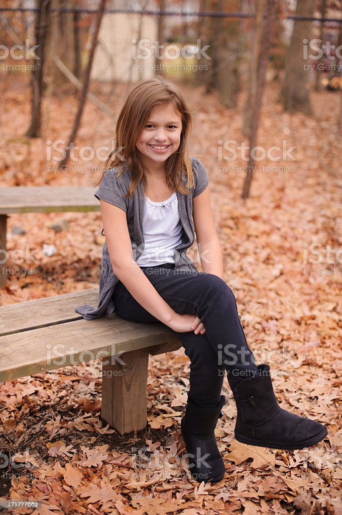 Cute Girl With Dimples Sitting on Bench During Fall royalty-free stock photo