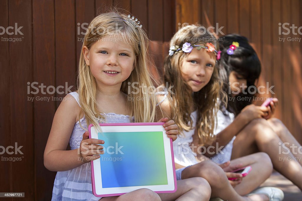 Jolie fille avec des amis montrant blanc tablette. photo libre de droits