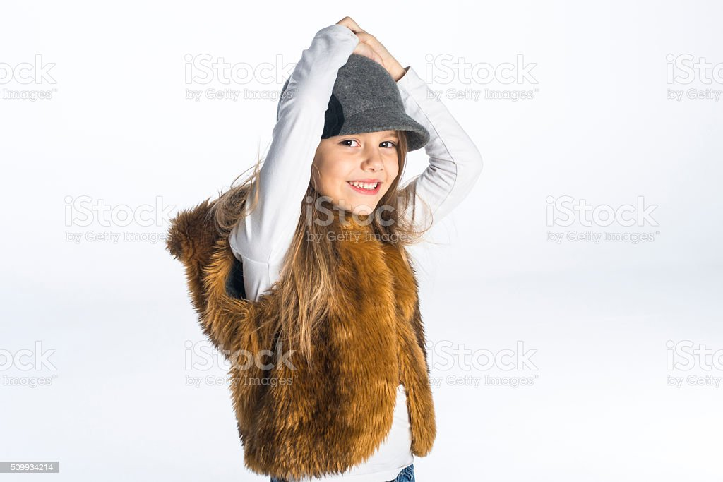 Cute girl with grey hat wearing a fur hooded vest stock photo
