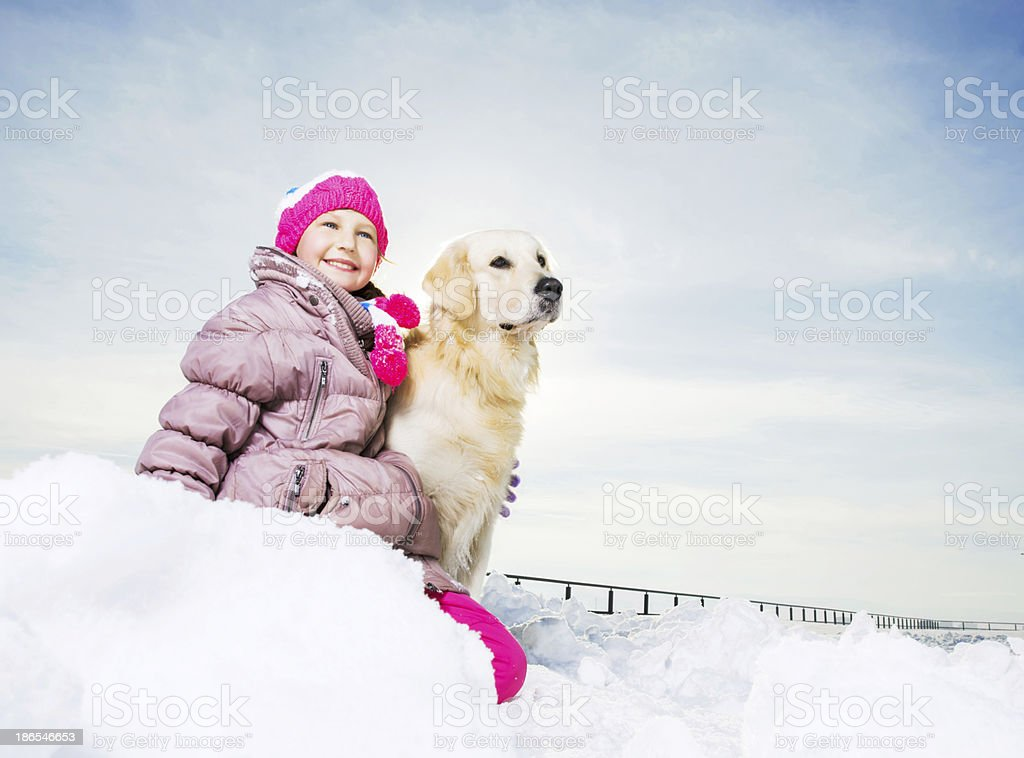 Cute girl with her dog enjoying in snow. royalty-free stock photo