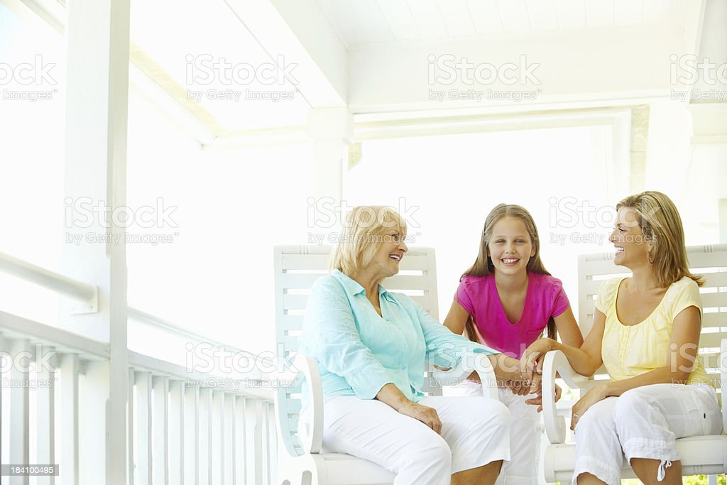 Cute girl with mother and grandmother on the porch royalty-free stock photo