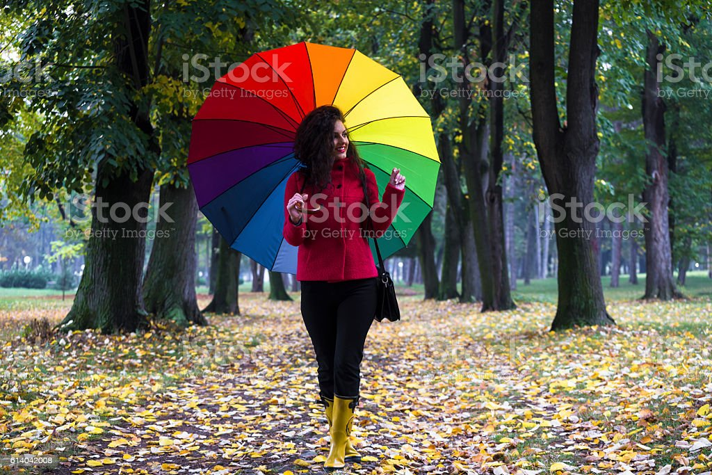 Cute girl with rainbow color umbrella walking in woodland park stock photo