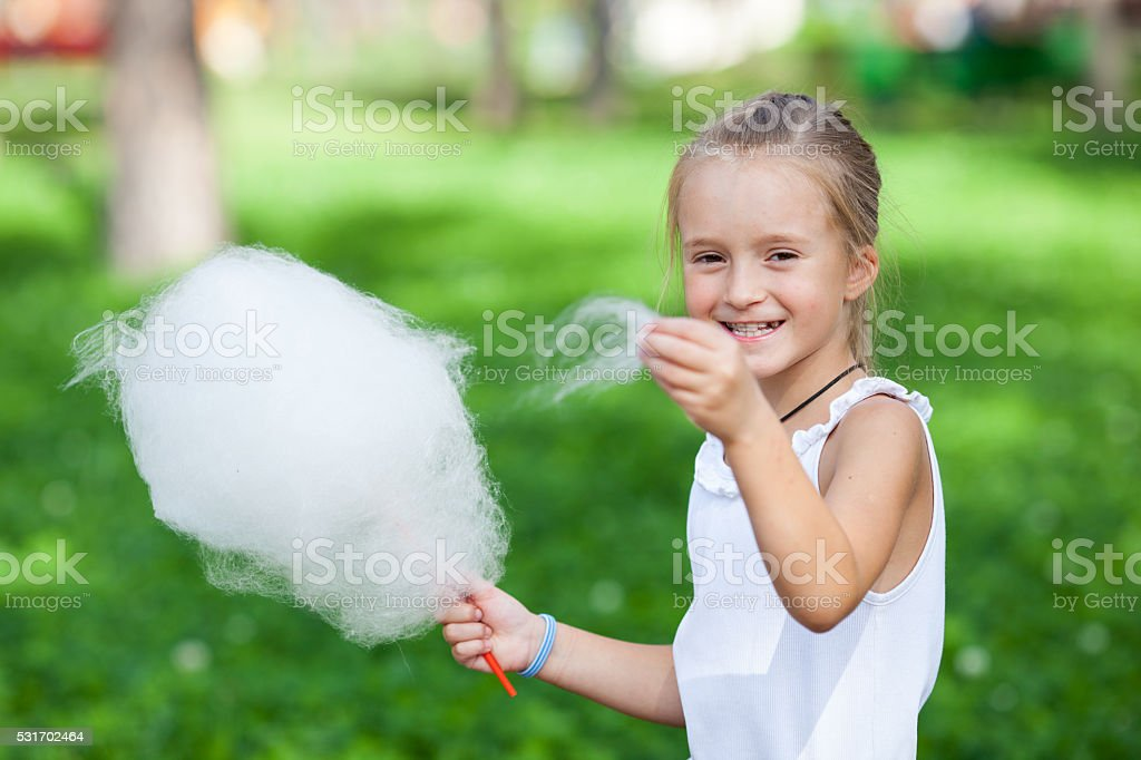 Cute girl with white cotton candy stock photo