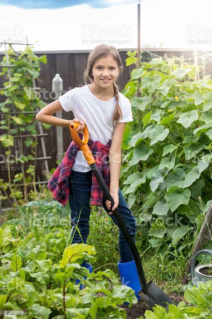 Cute girl working at garden and digging soil stock photo