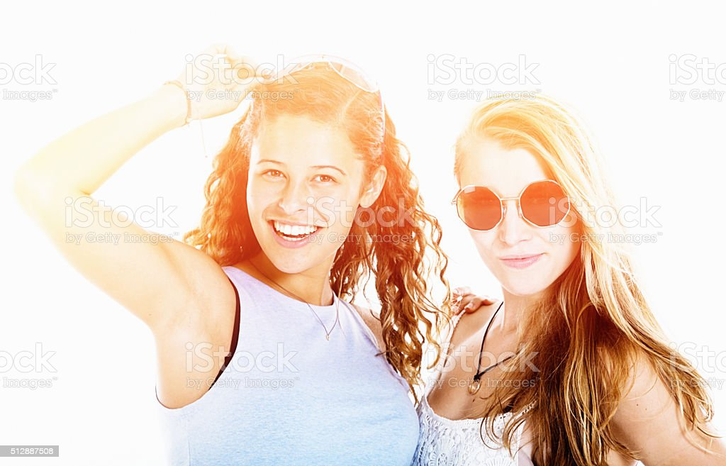 Cute girlfriends smiling happily in bright sunshine stock photo