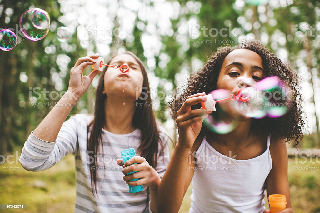 Cute girls blowing bubbles outdoors stock photo