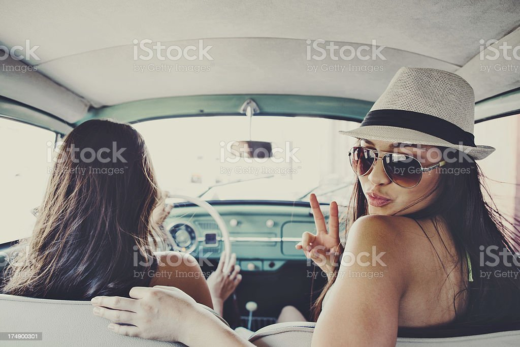cute girls in vintage car with peace sign royalty-free stock photo