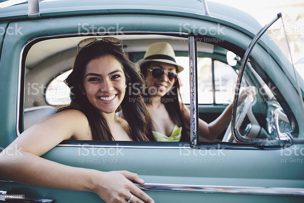 cute girls looking out of vintage car royalty-free stock photo
