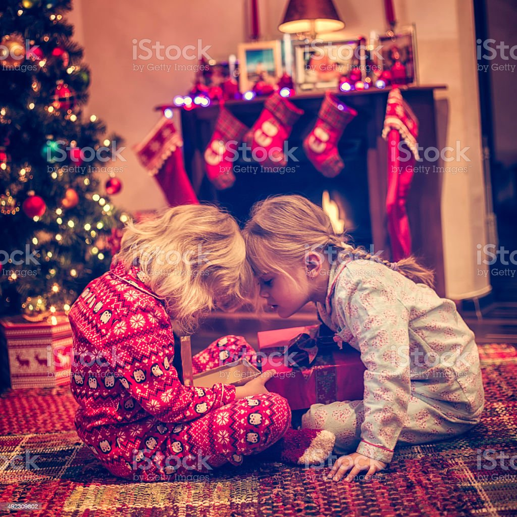 Cute Girls Opening Presents in in front of Christmas Tree stock photo