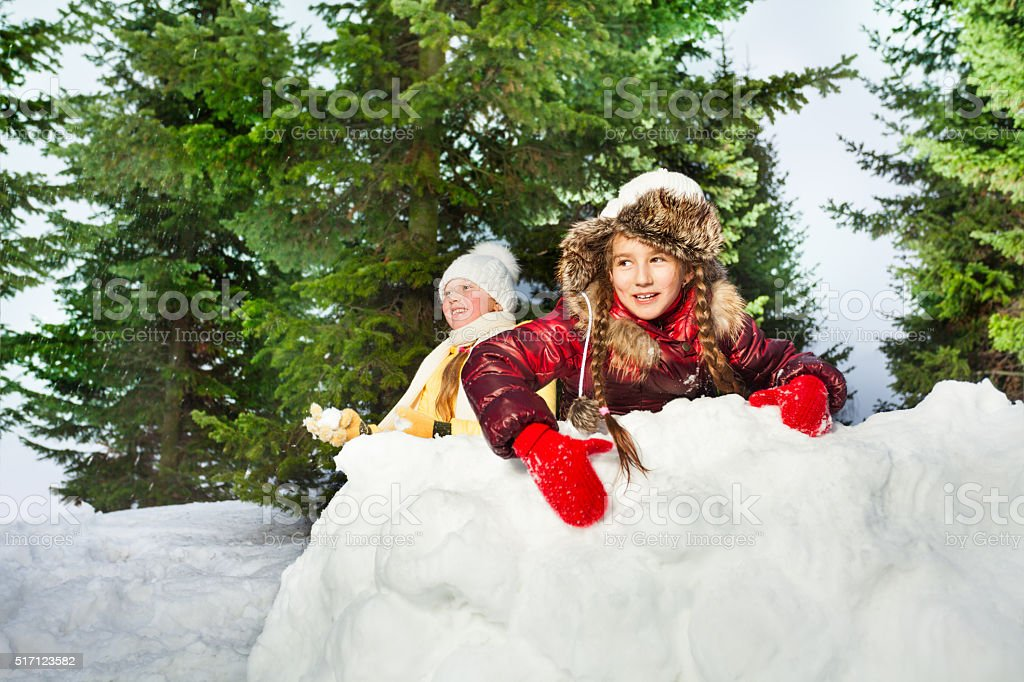 Cute girls playing the snowballs on a winter's day stock photo