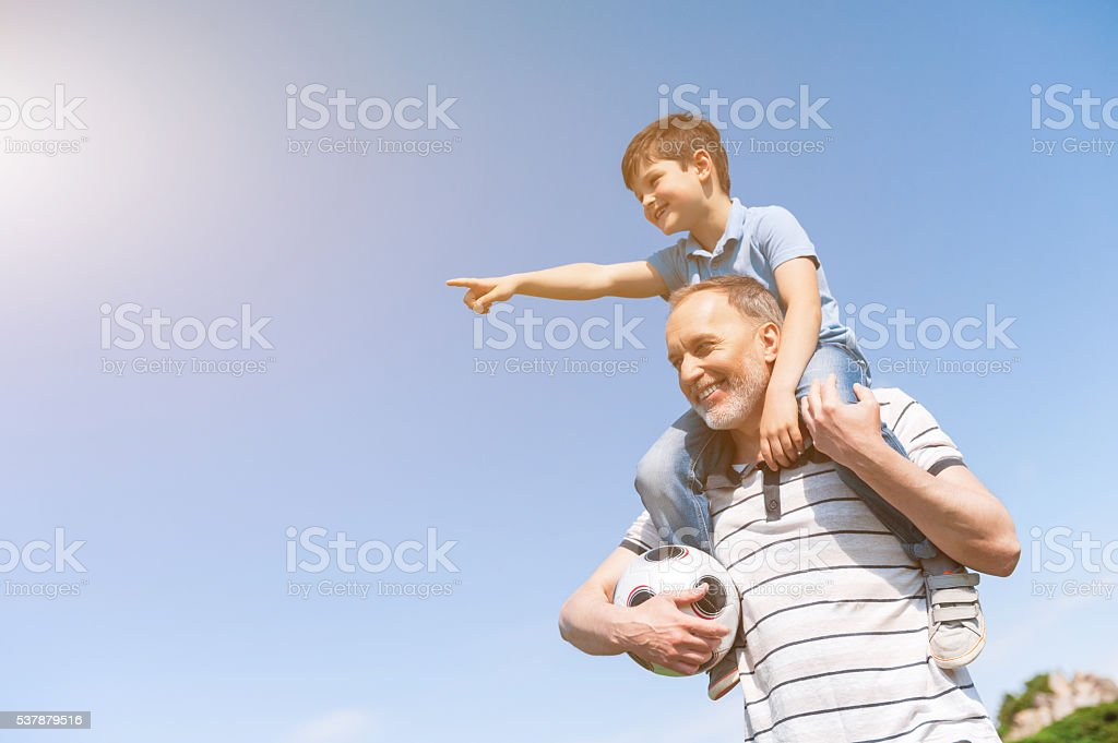 Cute grandson and grandparent are playing in park stock photo