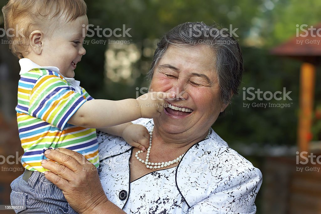 cute grandson grabbing nose of laughing grandmother. funny outdoors stock photo