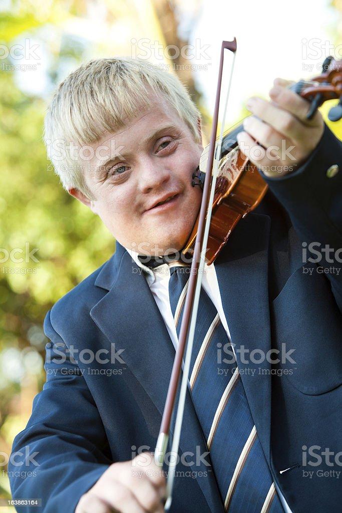 Adorable garçon jouant du violon pour personnes à mobilité réduite. photo libre de droits
