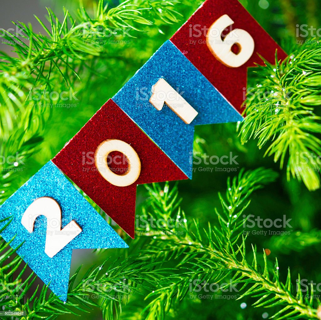 Cute handmade 2016 bunting hanging on Christmas tree branches stock photo